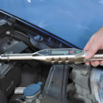 iq wrench torque wrench being used to tighten a bolt on the engine of a blue car